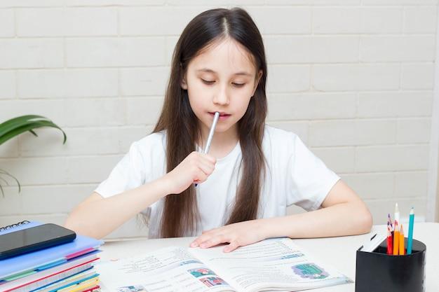 Uczennica ucząca się w domu i odrabiająca lekcje siedząca przy stole z podręcznikiem edukacji online