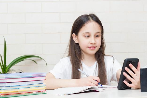 Uczennica ucząca się w domu, odrabiająca pracę domową, siedząca przy stole z podręcznikami na cyfrowym tablecie