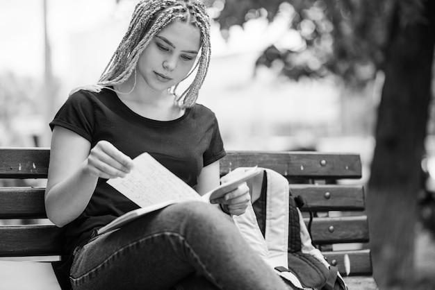 Uczennica uczenia się wykładu na ławce