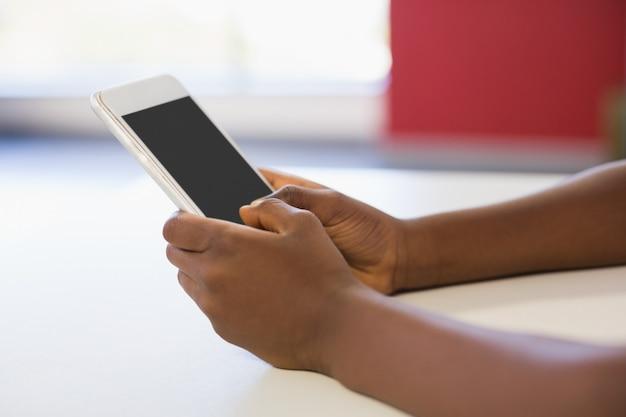 Uczennica używa telefon komórkowego w sala lekcyjnej