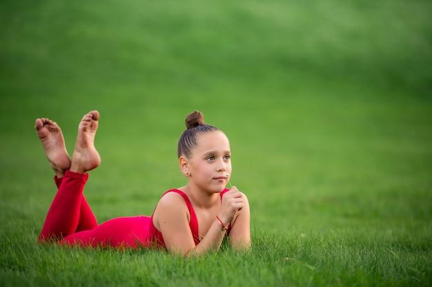 Uczennica w jaskrawoczerwonym kombinezonie uprawia gimnastykę na trawie, wykonując ćwiczenia rozciągające