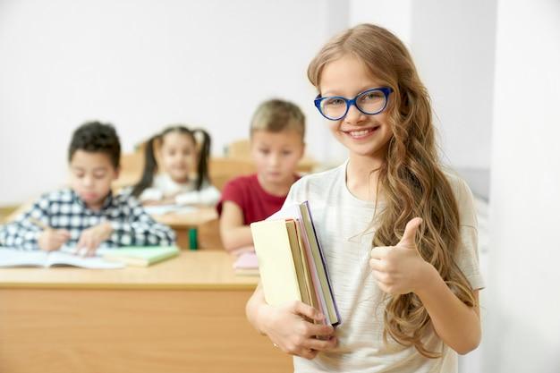 Uczennica w klasie gospodarstwa książek, pokazując kciuk do góry.