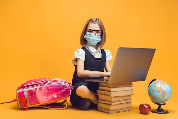 Uczennica w masce medycznej siedzi za stosem książek pracuje na laptopie edukacja dzieci w pandemii