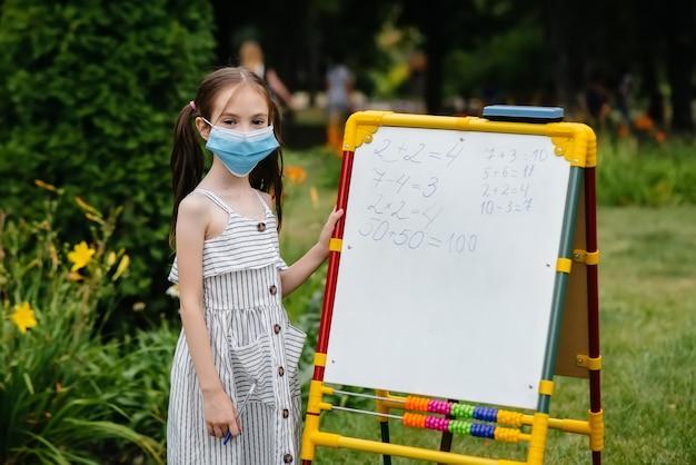 Uczennica w masce stoi i pisze lekcje na tablicy