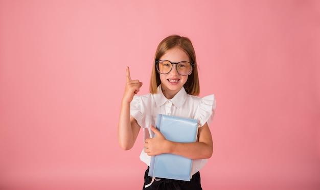 Uczennica w mundurku i okularach trzyma niebieski notatnik i wskazuje palcem na różowym tle z miejscem na tekst