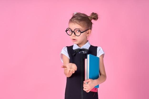 Uczennica w mundurowych i okrągłych okularach bez soczewek trzyma w rękach notatnik