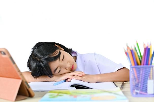 Uczennica w mundurze siedzącym spanie na stole w pobliżu tabletu i książki, koncepcja pochylania się lub egzaminu z nauczycielem e-learningowym online i drzemką lub uczyć się ciężko