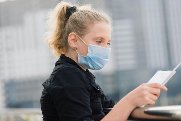 Uczennica w ochronnej masce medycznej o zachodzie słońca. współczesny uczeń z plecakiem podczas kwarantanny covid-19.