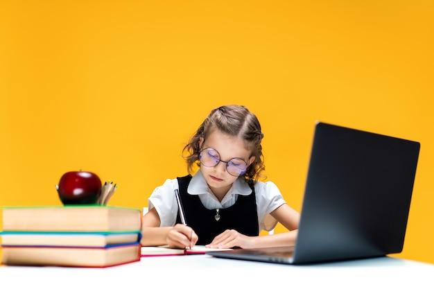 Uczennica w okularach pisze i siedzi przy laptopie podczas lekcji online nauki na odległość