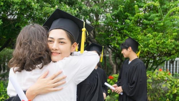 Uczennica w sukniach i kapeluszu graduation przytuliła rodzica podczas ceremonii gratulacyjnej.