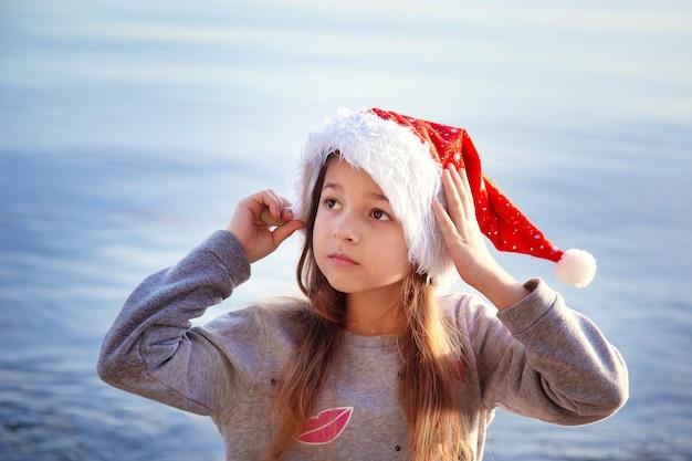 Uczennica w sylwestrowym kapeluszu siedzi nad brzegiem morza. boże narodzenie w ciepłych krajach. wakacje i święta sylwestrowe nad morzem