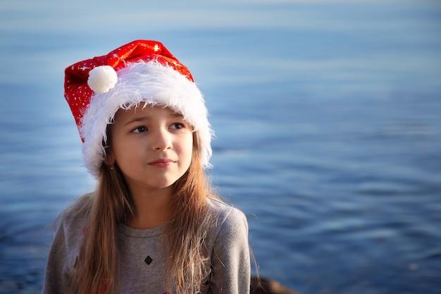 Uczennica w sylwestrowym kapeluszu siedzi nad brzegiem morza i marzy