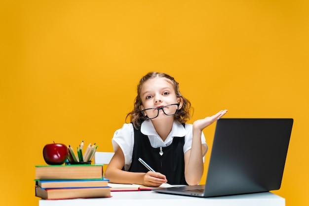 Uczennica w zabawie siedzi przy biurku z laptopem książki notebook edukacja na odległość