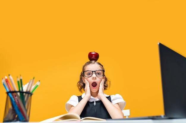 Uczennica w zabawie siedzi przy biurku z laptopem trzymając jabłko na głowie edukacja na odległość