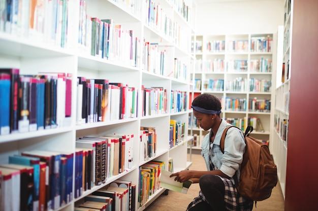 Uczennica wybiera książkę z półki z książkami w bibliotece