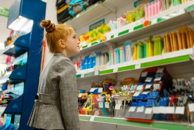 Uczennica wybierająca ołówek na półce w sklepie papierniczym