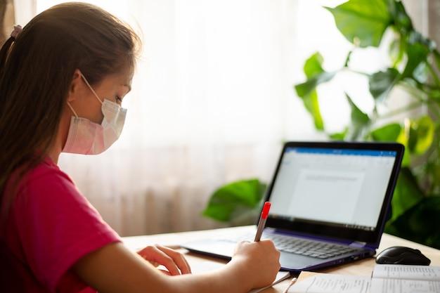 Uczennica wykonuje zadania szkolne w domu przez internet. kwarantanna koronawirusa i kształcenie na odległość