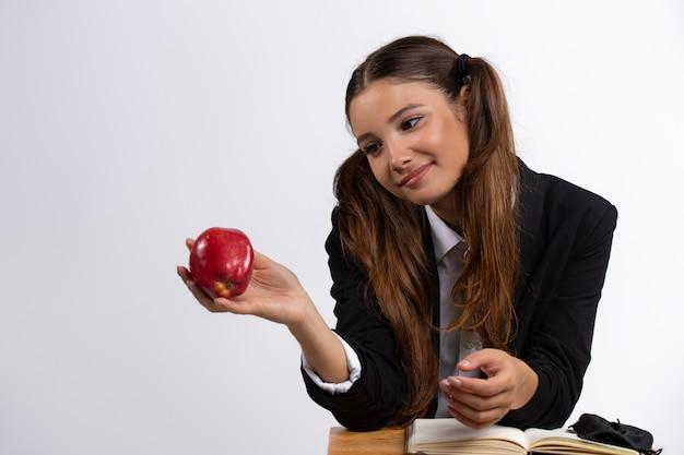 Uczennica z długimi włosami siedzi przy stole i patrzy na białą ścianę jabłka