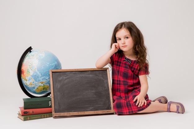 Uczennica z kulą ziemską, książkami i pustą deską kreślarską na białym tle