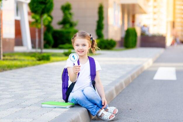 Uczennica z plecakiem i rachunkami w rękach siada na krawężniku w szkole i pokazuje numer jeden, koncepcja wraca do szkoły