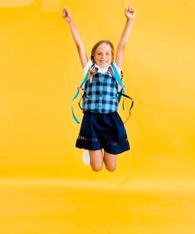 Uczennica z plecakiem skaczącym na żółtym tle