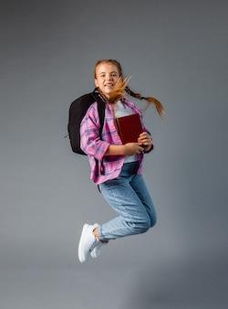 Uczennica z rbkzak skacze na szarym tle. treści szkolne