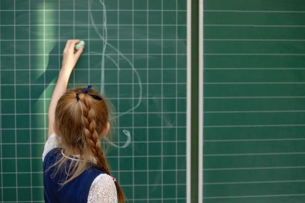 Uczennica z warkoczykami w mundurze pisze kredą na tablicy szkolnej. szkoła podstawowa. widok z góry. selektywna ostrość.