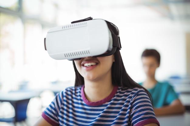 Uczennica za pomocą zestawu słuchawkowego wirtualnej rzeczywistości w klasie