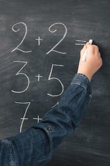 Uczennica zapisująca sumy matematyczne kredą na tablicy