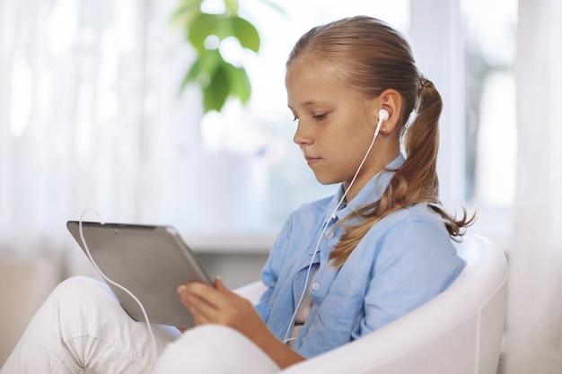 Uczennica ze słuchawkami siedzi na krześle z tabletem i odrabia lekcje podczas lekcji online.