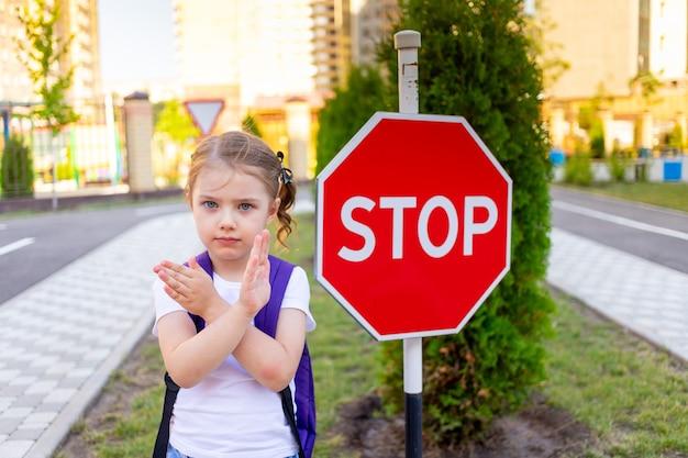 Uczennica ze znakiem stop przechodzi przez ulicę lub uczy się zasad ruchu drogowego