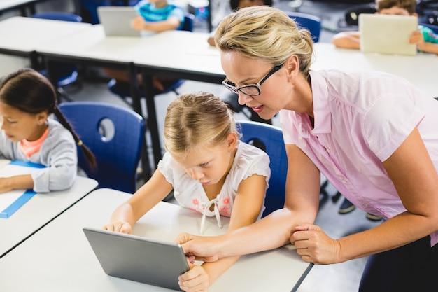 Uczennice i nauczyciel za pomocą cyfrowego tabletu w klasie