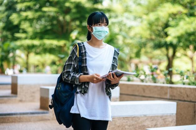 Uczennice noszą maski, stoją na schodach i trzymają książki.