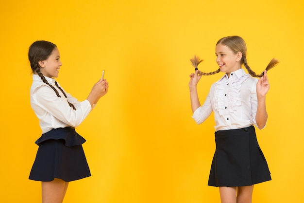 Uczennice robią zdjęcie za pomocą smartfona. mundurek szkolny dla dziewcząt. blog osobisty. nie podawaj nikomu swojego hasła ani żadnych informacji o swojej rodzinie. życie w internecie. szkolny smartfon aplikacji.
