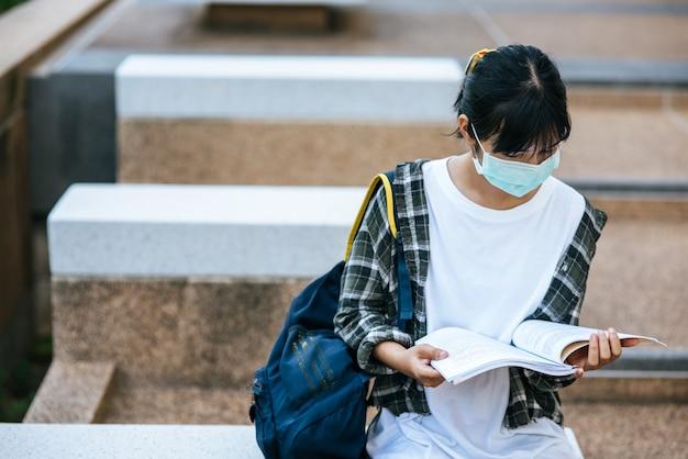 Uczennice w maskach i książkach na schodach.