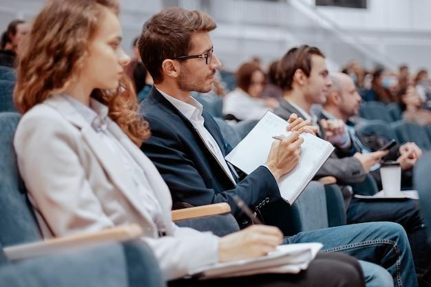 Uczestnicy seminarium biznesowego robiący notatki w swoich zeszytach