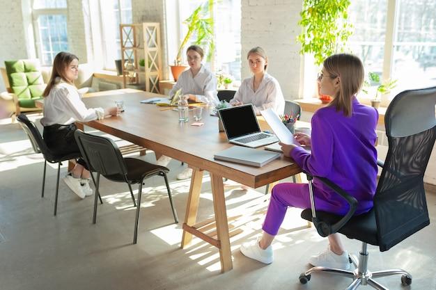 Uczestniczył. młoda biznesowa kaukaski kobieta w nowoczesnym biurze z zespołem.