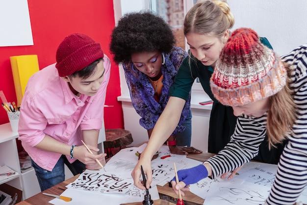 Uczęszczanie na lekcje mistrzowskie. widok z góry młodych kreatywnych, utalentowanych przyszłych artystów uczęszczających na lekcje mistrzowskie