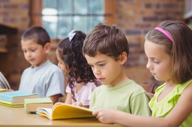 Ucznie czyta książki w bibliotece