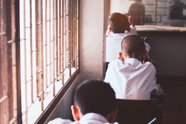 Ucznie czytają i robi egzaminowi w sala lekcyjnej z stresem