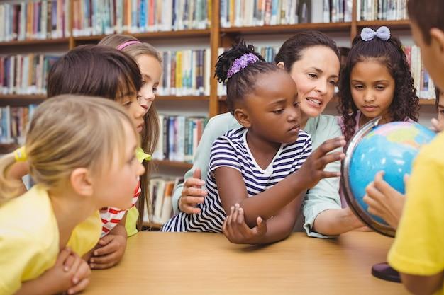 Ucznie i nauczyciel patrzeje kulę ziemską w bibliotece