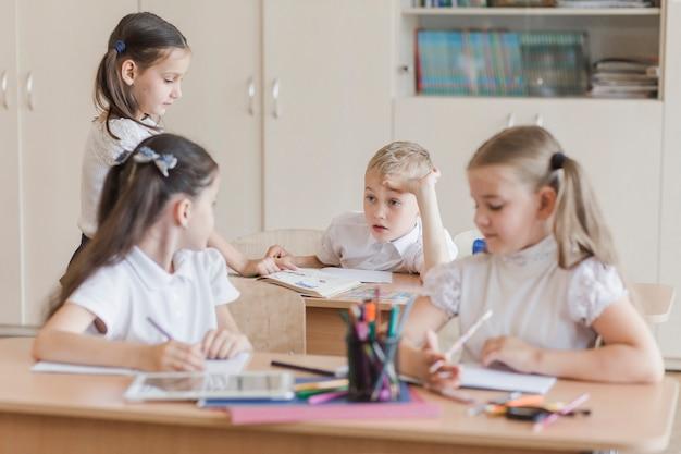 Ucznie opowiada w sala lekcyjnej obsiadaniu przy biurkami