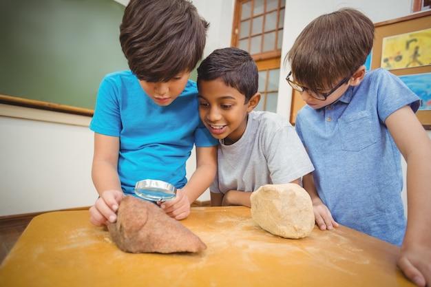 Ucznie patrzeje kamień z powiększać - szkło