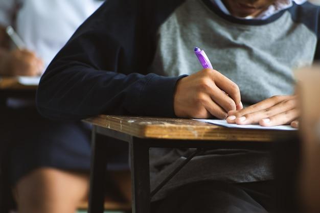Ucznie pisze piórze w ręce robi egzaminom odpowiadają prześcieradła ćwiczą w sala lekcyjnej z stresem.
