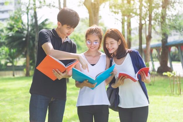 Ucznie trzyma książki i opowiada podczas gdy stojący w parku. edukacja w szkole lub na uniwersytecie