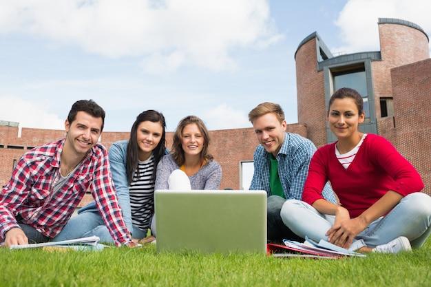 Ucznie z laptopem w gazonie przeciw szkoła wyższa budynkowi