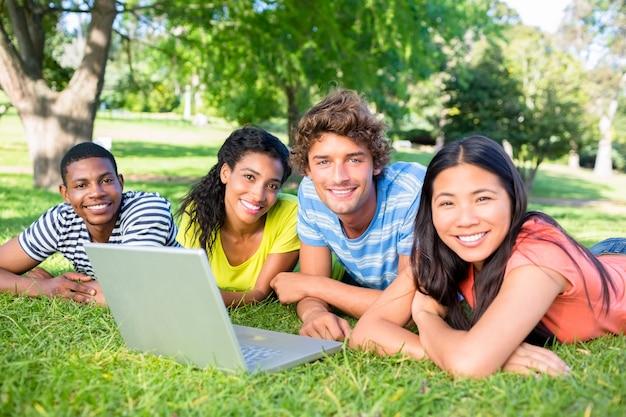 Ucznie z laptopu lying on the beach na kampusie