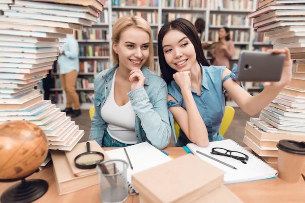Uczniowie biorą selfie w szkolnej bibliotece.