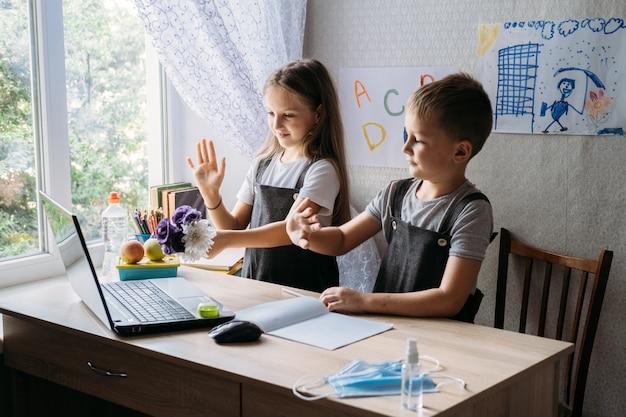 Uczniowie, chłopiec i dziewczynka, korzystający z laptopa do nauki online podczas nauki w domu w domu