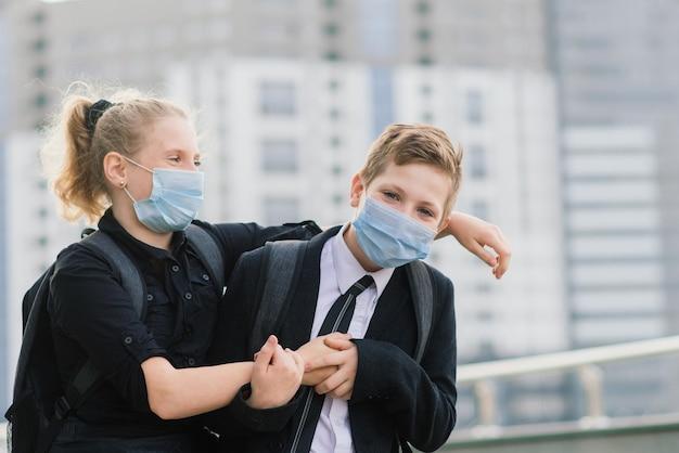 Uczniowie, chłopiec i dziewczynka w maskach medycznych spacerują po mieście.